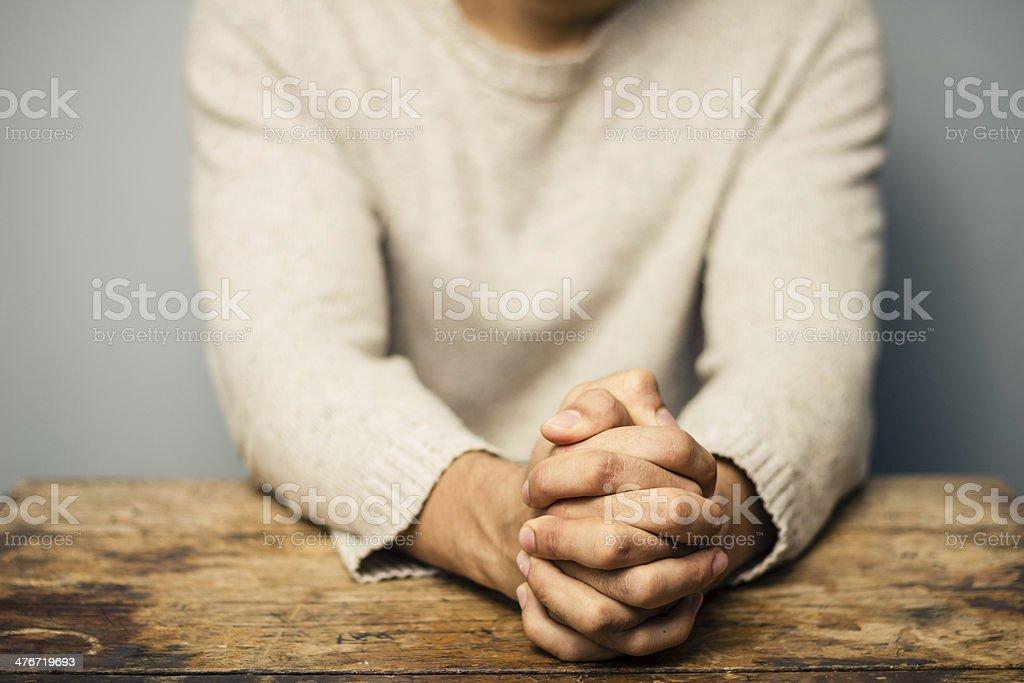 Praying man at desk royalty-free stock photo