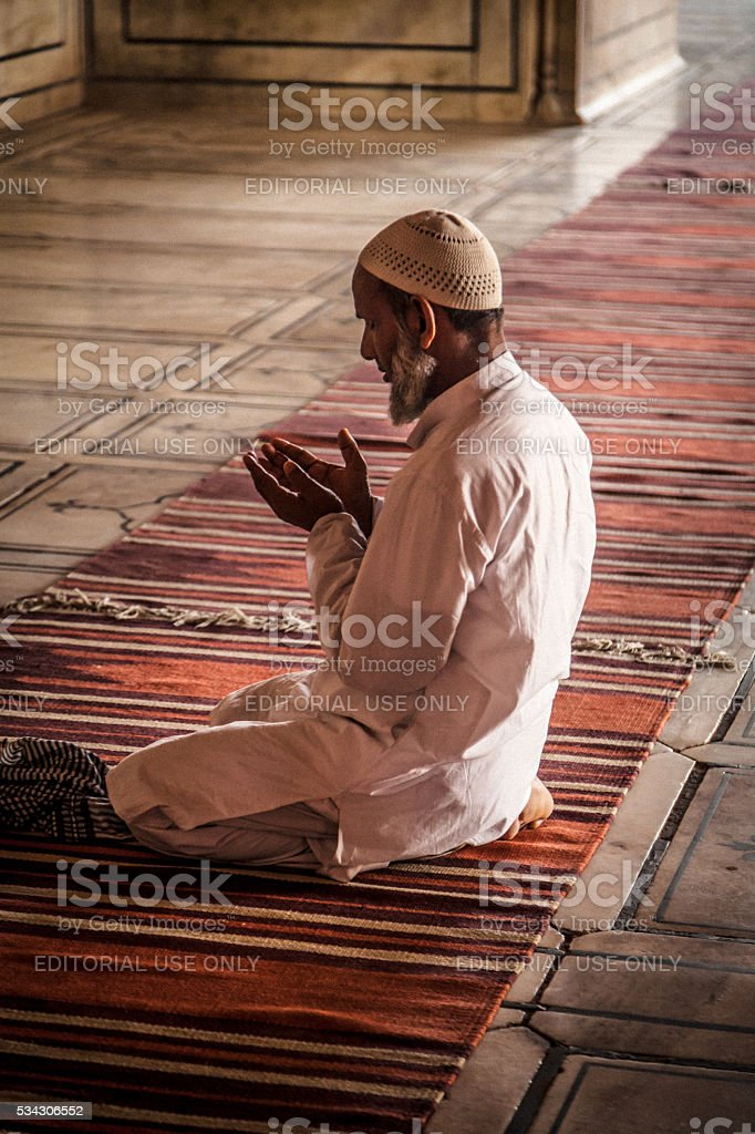 Praying man in Jama Masjid Mosque stock photo