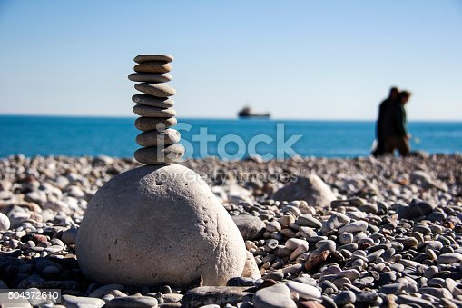 istock Praying man silhouette on the beach and stones balance. 504372610