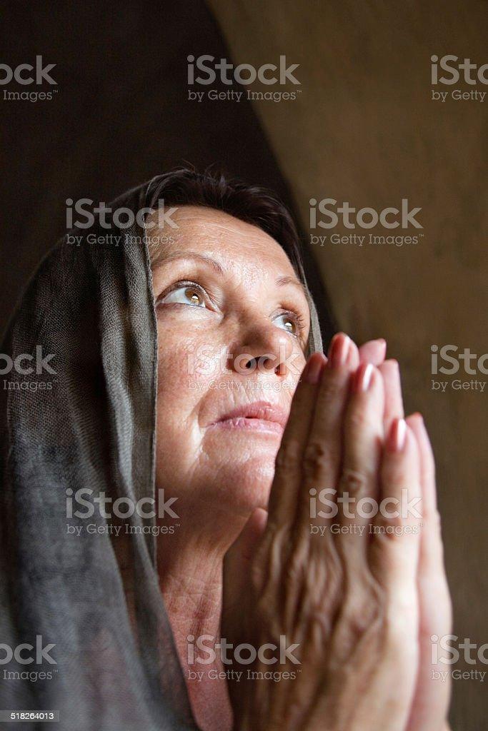 Praying mature woman stock photo