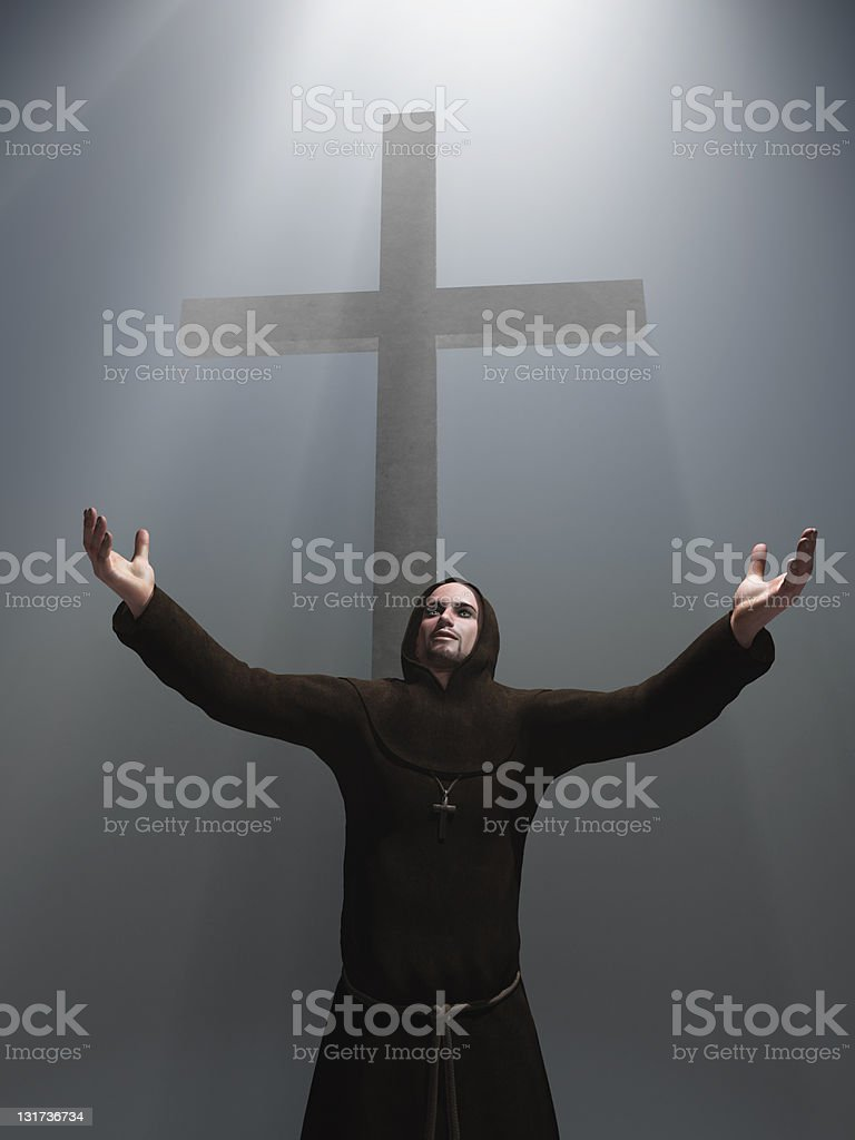 praying monk before a cross stock photo