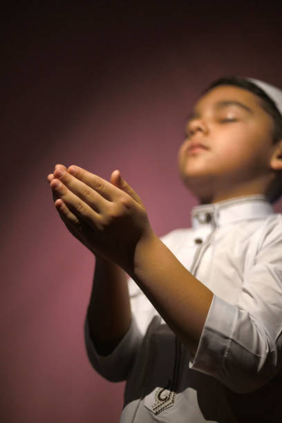 Praying Muslim boy Muslim child praying in the mosque. Little middle-eastern boy prays to God and thanks. Peace and love in the holy month of Ramadan rohingya culture stock pictures, royalty-free photos & images