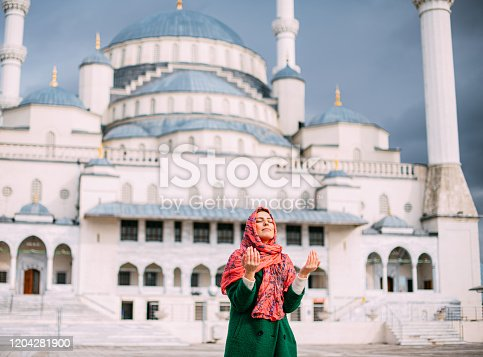 Muslim Woman Praying in Front of Mosque