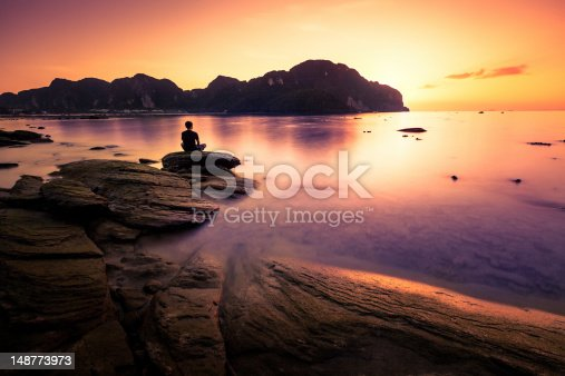 Man sitting in loto position on a rock of Phi Phi island, Thailand.