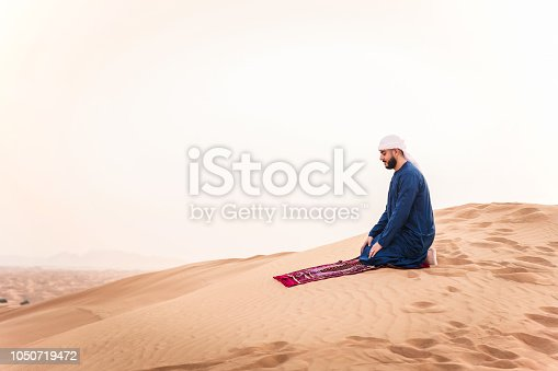 istock Praying on the sand dunes 1050719472