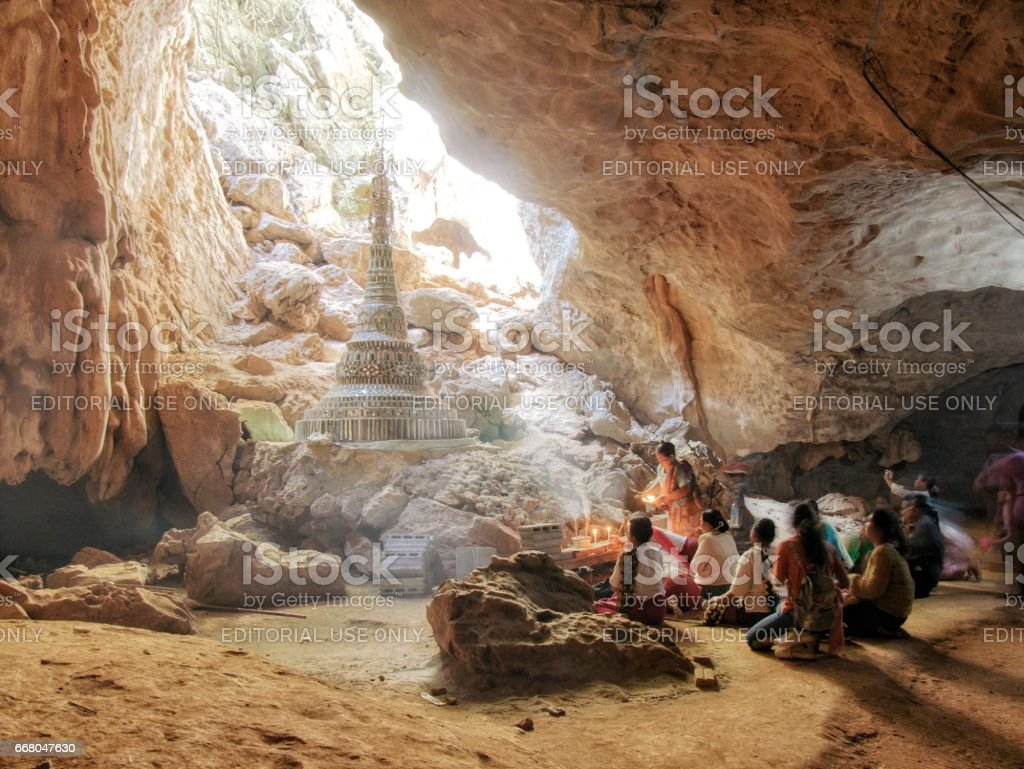 Praying people in front of stupa in saddan cave stock photo