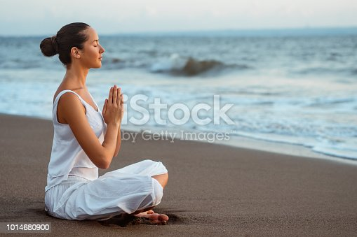 Meditating woman on the beach
