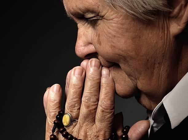 Praying senior woman. stock photo