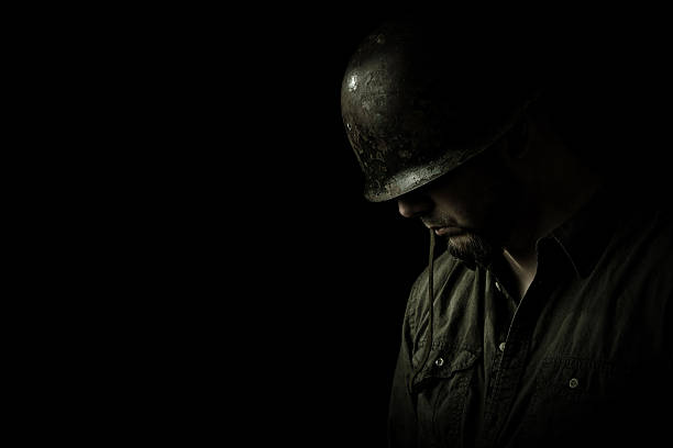 Praying Soldier Soldier in dramatically soft lighting with his head bowed in prayer. post traumatic stress disorder stock pictures, royalty-free photos & images
