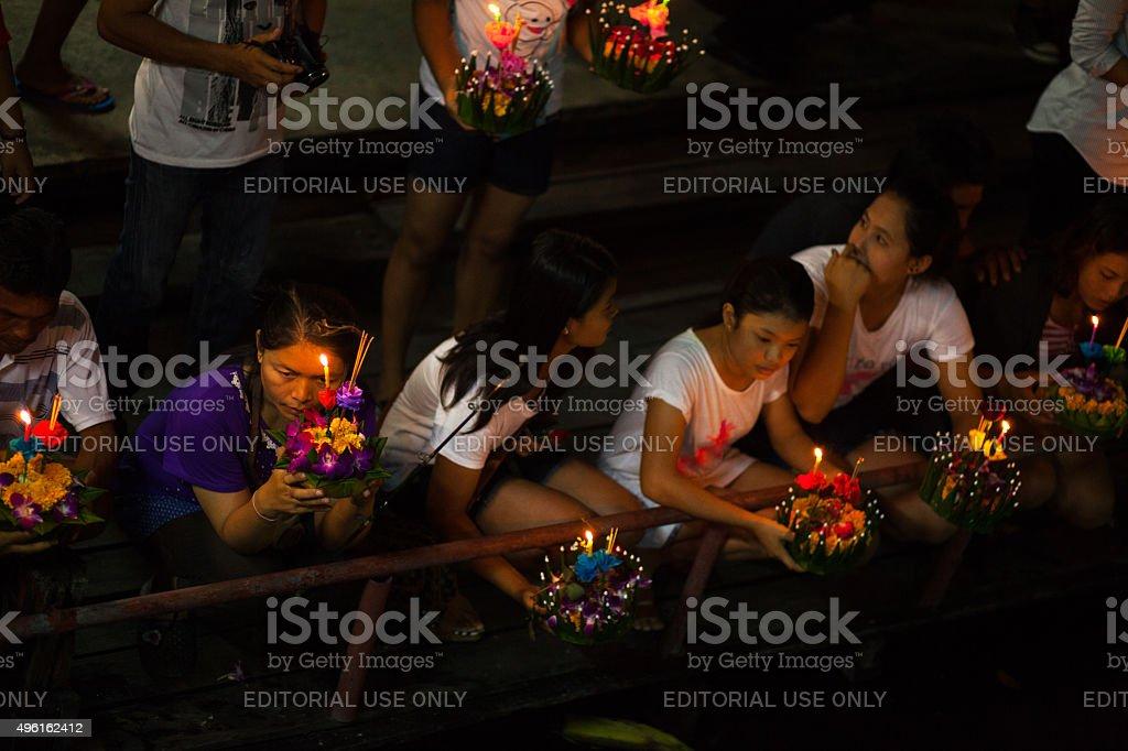 Praying thai women at river Ladprao Bangkok, Thailand - November 6, 2014: Aerial shot of praying thai women at river and canal Ladprao in Bangkok Ladprao in Loy Krathong night. View down from bridge behind Wat Siri to women with flowers and candles. 2015 Stock Photo