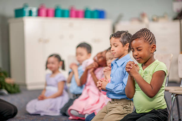 praying together in class - african american church stock pictures, royalty-free photos & images