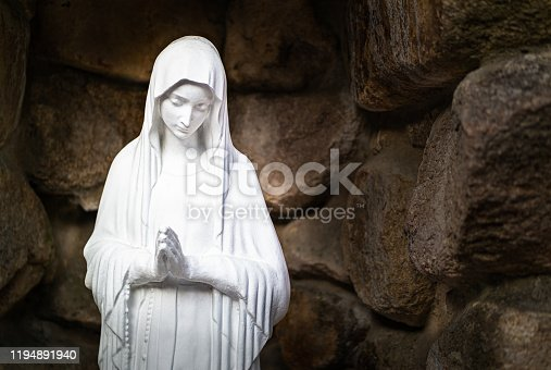 On the corner of a small cathedral, there is a statue of the Virgin Mary praying in a stone-covered place.