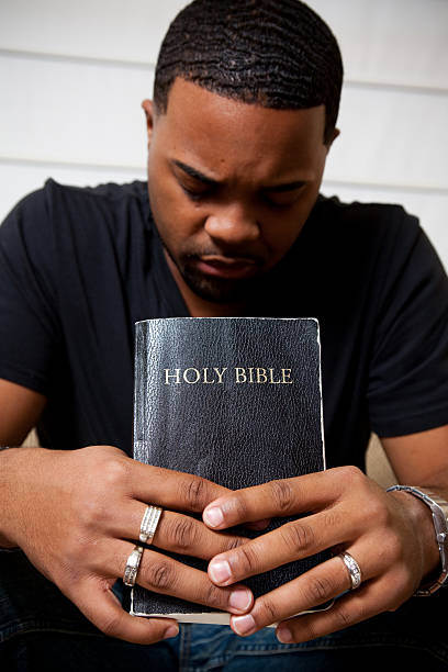 Praying while holding the Bible stock photo