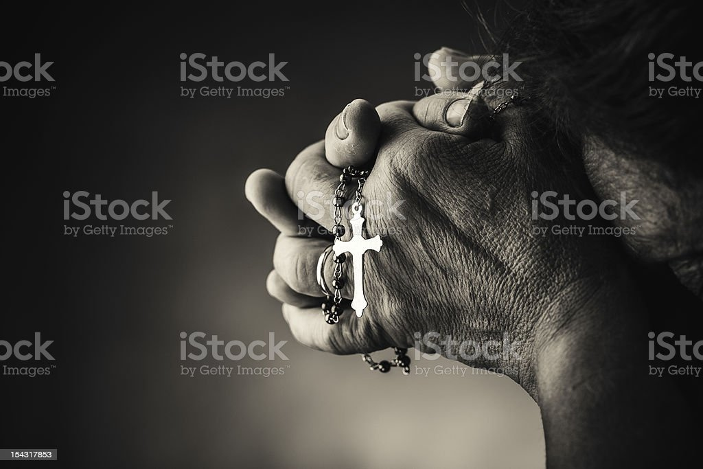 Praying with a rosary royalty-free stock photo
