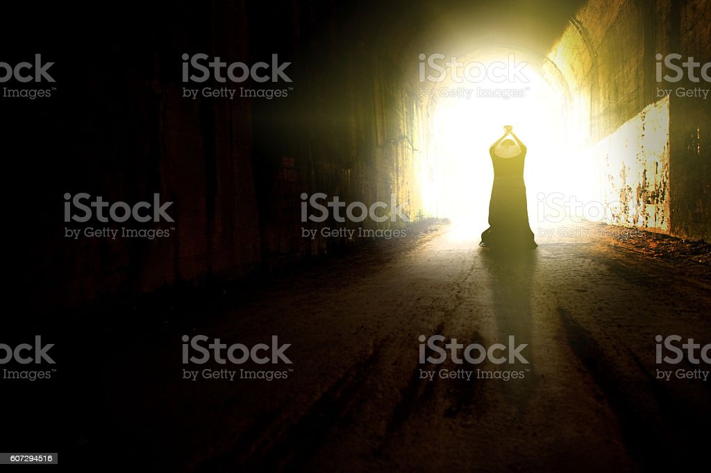 Praying Woman At End Of Tunnel stock photo