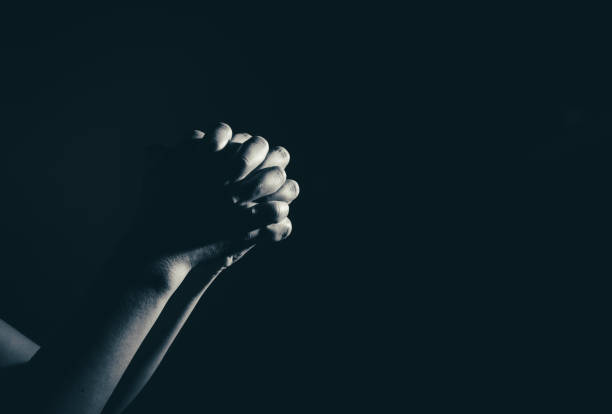 praying woman hand in the dark ( praying in secret room concept ) stock photo