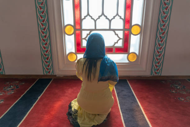 Praying young muslim woman. Middle eastern girl praying and reading the holy Quran. Muslim woman studying The Quran at the mosque stock photo