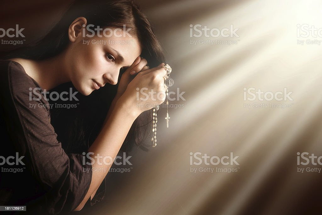 Praying young woman in divine light royalty-free stock photo
