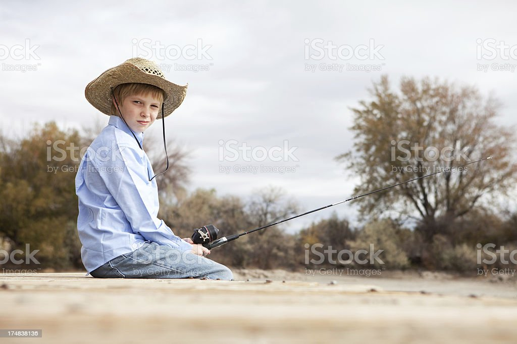 Pre Adolescent Boy Wearing Cowboy Hat Sitting and Fishing royalty-free stock photo