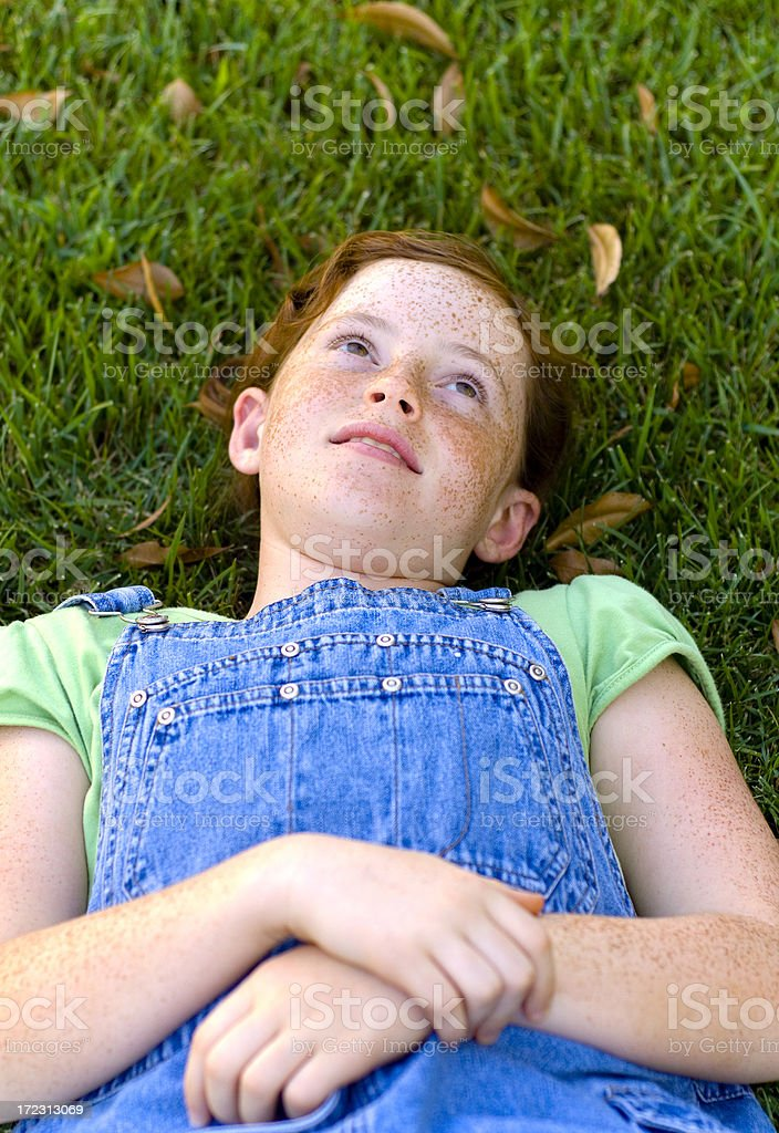 Pre Adolescent Girl, Redhead Child Daydreaming on Park Grass stock photo