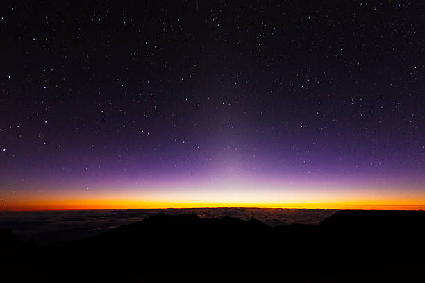 Pre Dawn Starry Sky Haleakala National Park Maui Hawaii USA This is a horizontal, color, royalty free stock photograph of a  multicolored sky. The warm orang and yellow glow of the sunrise peaks above the horizon near the summit of Haleakala National Park in Maui, Hawaii. The night sky is deep purple and filled with stars. Photographed with a Nikon D800 DSLR camera. fresh start morning stock pictures, royalty-free photos & images