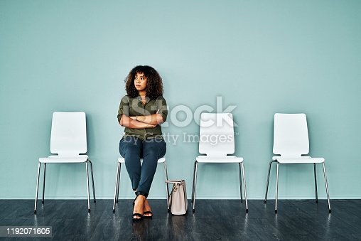 Studio shot of a young businesswoman waiting in line against a blue background