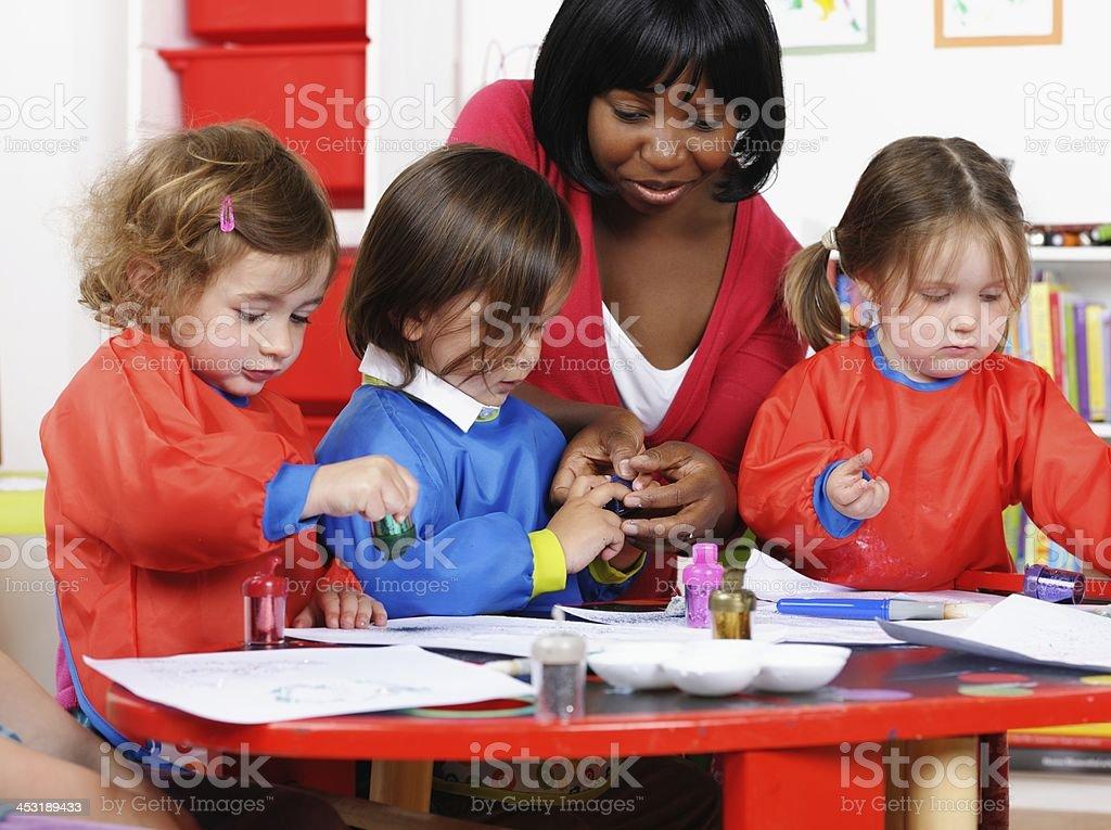 Pre School Children Enjoying Art And Craft With Carer stock photo