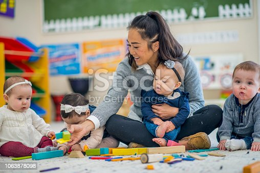 a young female teacher sits cross-legged on the floor while she plays with a few babies. She holds on in her lap while she passes some blocks to another. A little boy is off on the side drooling.