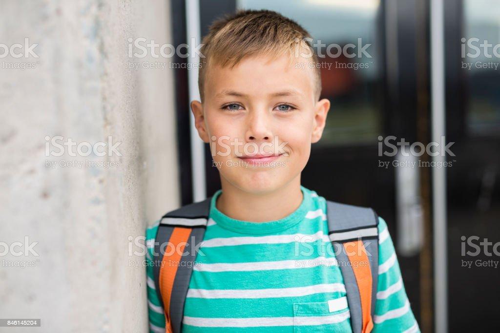 Pre teen boy outside at school stock photo