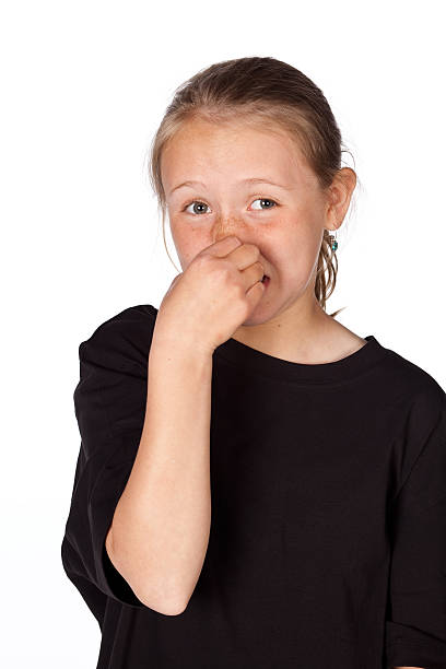 Pre teen girl holding her nose isolated on white. stock photo