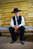 Senior Preacher sitting on his simple wooden bed, thinking. Traditional Wild West Portrait.