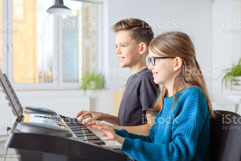 Pre-adolescent friends playing piano in class Smiling boy and girl playing piano in music class. Pre-adolescent friends are learning music in training class. They are in casuals at conservatory. 10-11 Years Stock Photo
