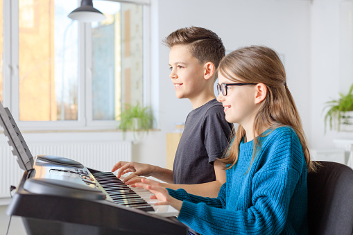 Preadolescent Friends Playing Piano In Class Stock Photo - Download Image Now