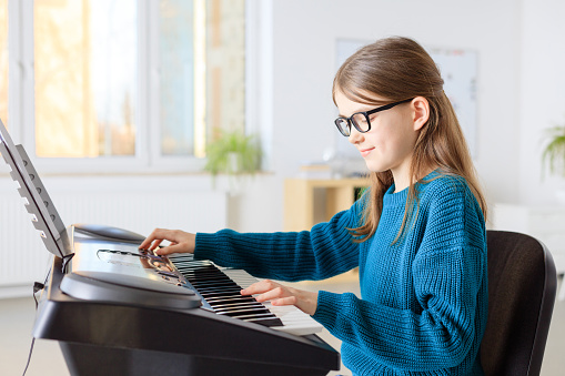 Preadolescent Student Playing Piano In Classroom Stock Photo - Download Image Now