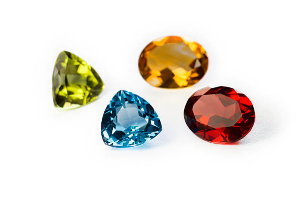 Precious Gemstones Garnet Imperial Topaz Ruby and Sapphire Closeup of precious (from top left clockwise:Garnet,Imperial Topaz,Ruby and Sapphire) gemstones on white background stone object stock pictures, royalty-free photos & images