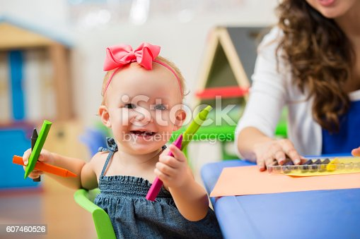 Cute little toddler girl sitting at a table and playing with crayons with her teacher in the background. She is holding the crayons and smiling at the camera.