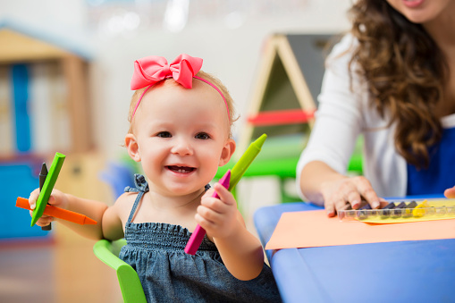 istock Precious happy toddler girl in preschool playing with crayons 607460526