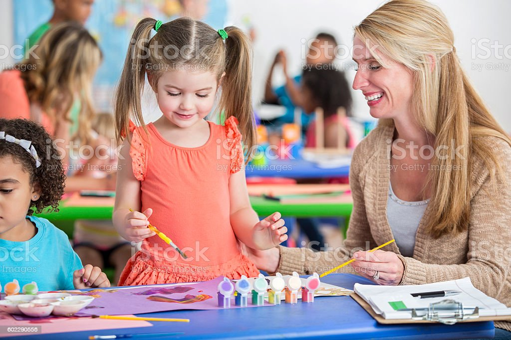 Precious little girl with pigtails paints a picture in daycare stock photo