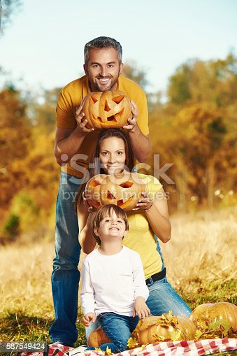 happy family in the autumn laughing and enjoying spending time together in autumn day.holding Halloween pumpkins.