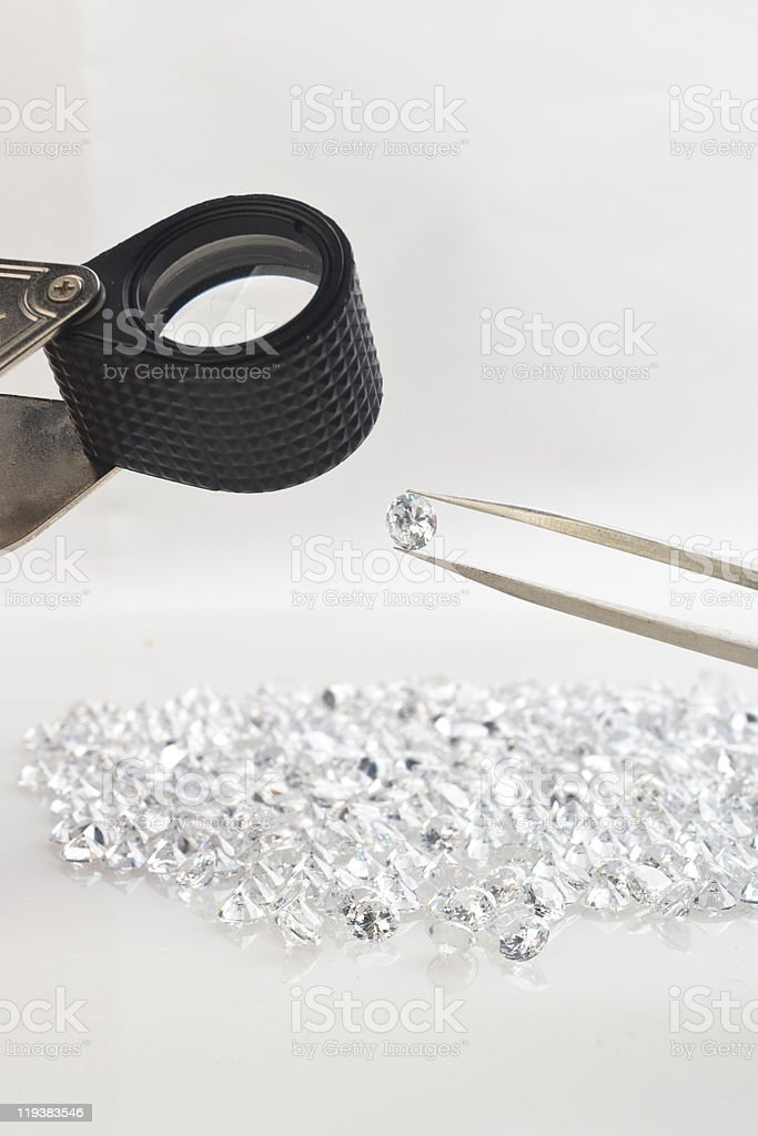 Precious stone with equipment of loupe and tweezer stock photo