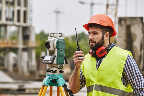 precise measurements. surveyor engineer in protective wear and red helmet using geodetic equipment and talking by walkie talkie while standing at construction site. professional equipment. - ricetrasmettitore foto e immagini stock