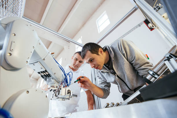 precise mechanics on robotic arm in industry - automated stock photos and pictures