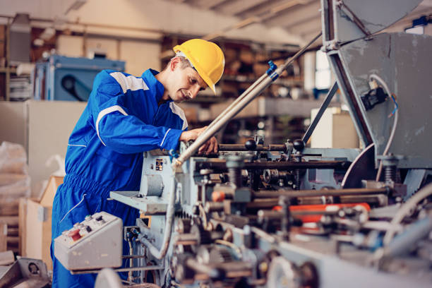 Precision mechanics in industry Maintenance engineer or blue collar worker working in production factory, testing and repairing machines, testing roll bars and using grinder or drill. mechanical engineering stock pictures, royalty-free photos & images