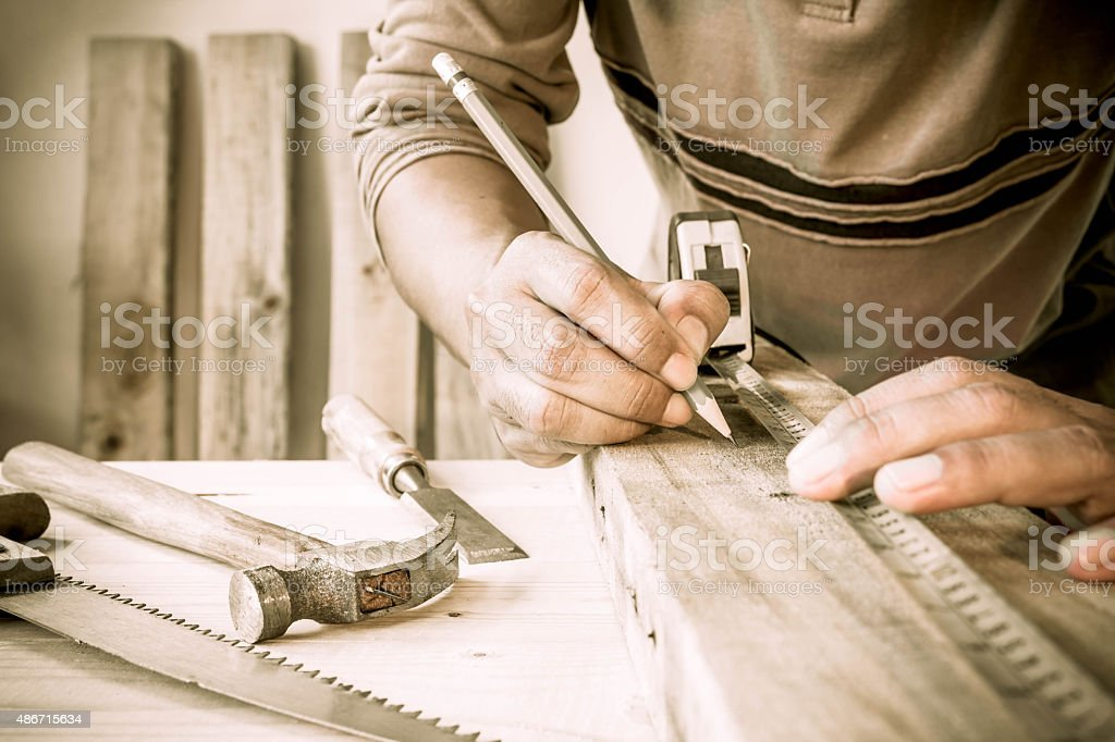 Precision throughout. Serious young male carpenter working with wood. stock photo