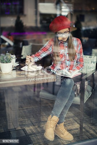 istock Preety young woman sitting in coffee shop and drinking tea 926293232