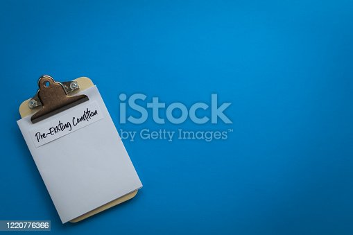 Pre-Existing Condition healthcare concept on clipboard, flat lay on blue background