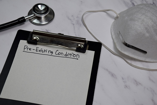 Pre-Existing Condition write on clipboard isolated on office desk