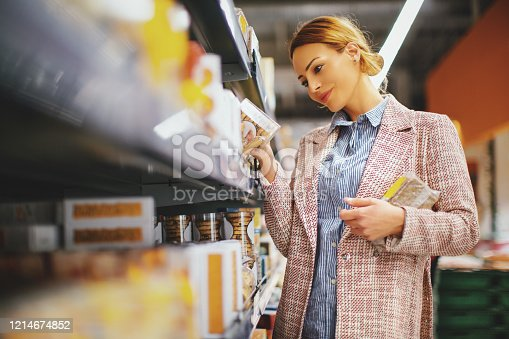 Young woman buying gluten free bread and cookies at supermarket.