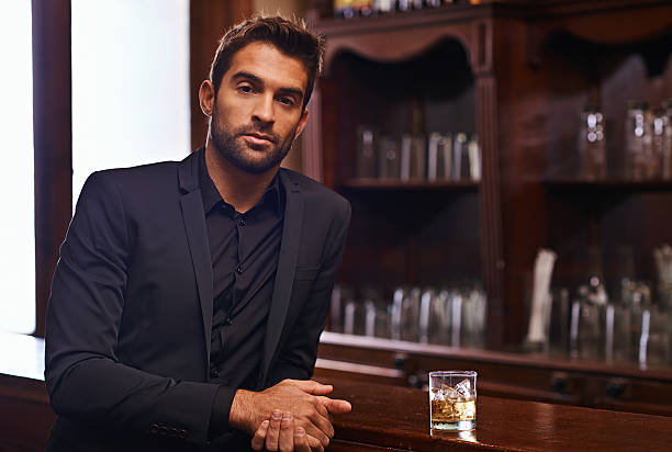 I prefer whiskey Cropped shot of a handsome and confident young man charming stock pictures, royalty-free photos & images