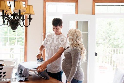 802472024 istock photo Pregant woman looking a men ironing 583694764